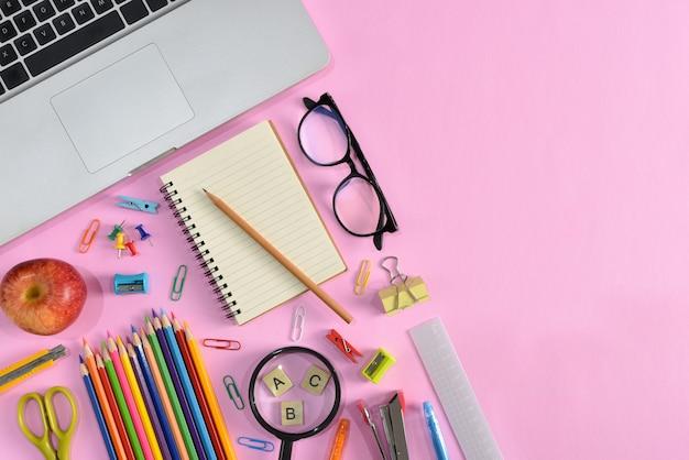 Vista superior de papelería o útiles escolares con libros, lápices de colores, calculadora, computadora portátil, clips y manzana roja sobre fondo rosa.