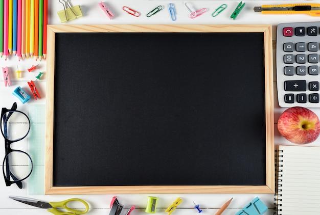 Vista superior de papelería o útiles escolares con libros, lápices de colores, calculadora, fondo de pizarra en blanco con copyspace