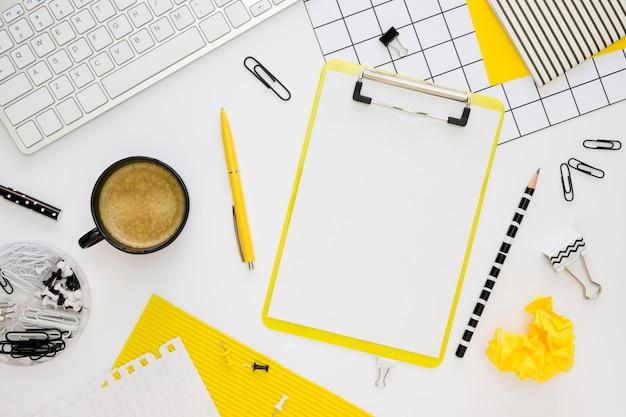 Vista superior de papelería de oficina con bloc de notas y café