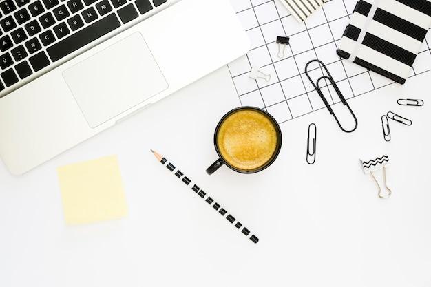 Vista superior de papelería de oficina con café y computadora portátil