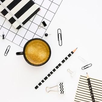 Vista superior de papelería de oficina con café y lápiz.