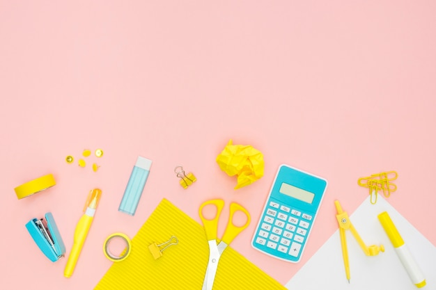 Vista superior de papelería de oficina con calculadora y borrador