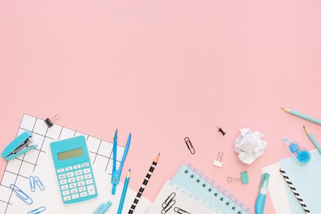 Vista superior de papelería de oficina con calculadora y espacio de copia