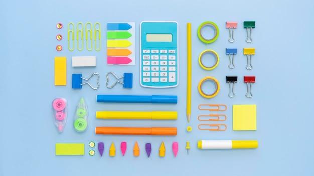 Vista superior de papelería de oficina colorida con calculadora y clips