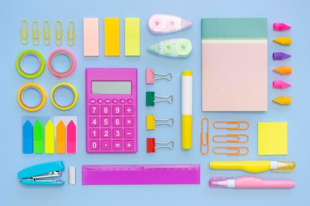 Vista superior de papelería de oficina colorida con calculadora y grapadora