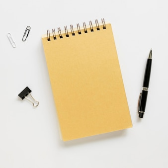 Vista superior de papelería de oficina con cuaderno y bolígrafo