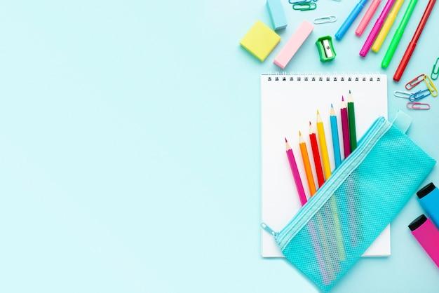 Vista superior de papelería de regreso a la escuela con copia espacio y lápices de colores