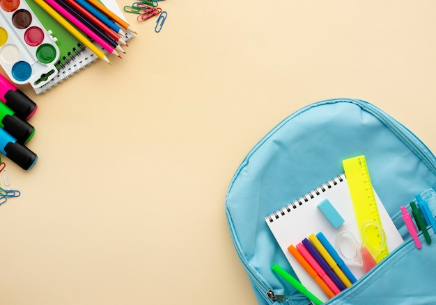 Vista superior de papelería de regreso a la escuela con mochila y lápices de colores