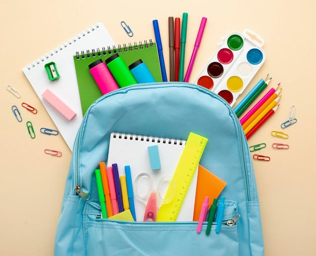 Vista superior de papelería de regreso a la escuela con mochila y lápices de colores.