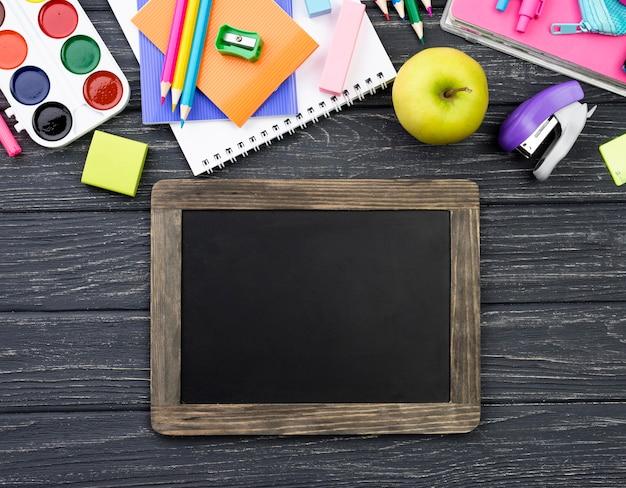 Vista superior de papelería de regreso a la escuela con pizarra y manzana