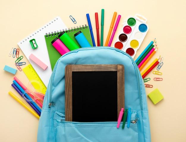 Vista superior de papelería de regreso a la escuela con pizarra y mochila