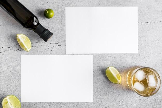 Vista superior de papeles de menú en blanco con aceite de oliva y bebida