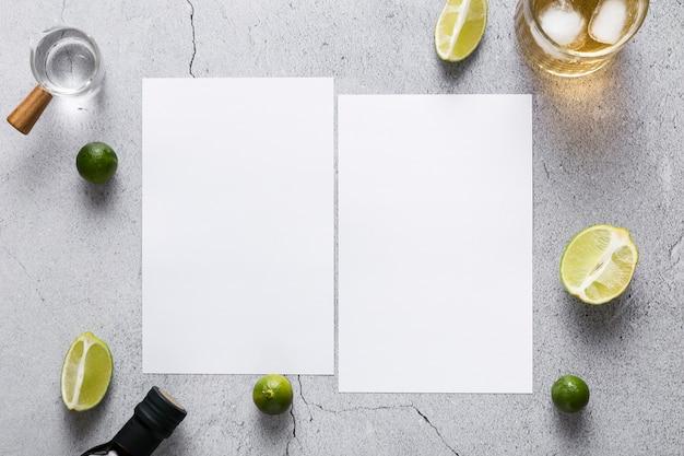 Vista superior de papeles de menú en blanco con limas y bebida