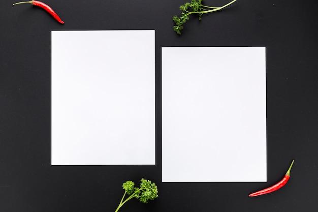 Vista superior de papeles de menú en blanco con pimientos y vegetación