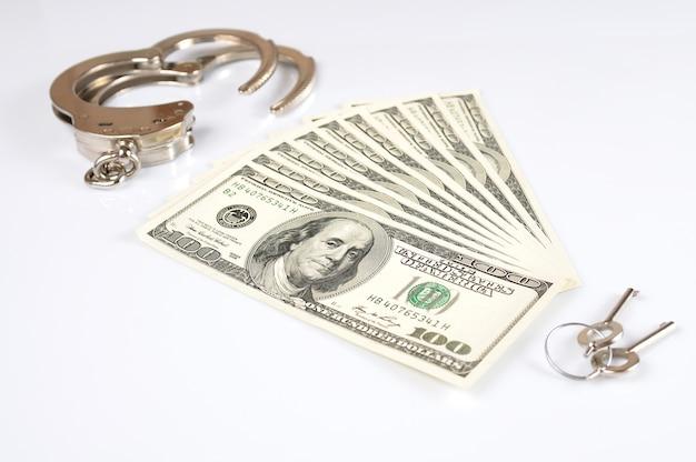 La vista superior de un paquete de billetes de cien dólares, esposas y llaves se encuentran sobre una mesa blanca. concepto de delito sobre la base de las finanzas y la dependencia del bienestar financiero