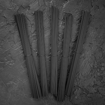 Vista superior de paquetes de espagueti negro en pizarra