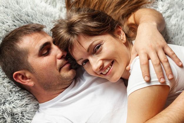 Vista superior pareja abrazándose y sentado en la cama