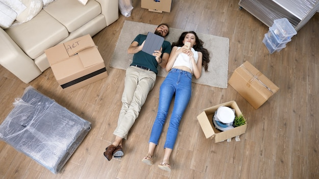 Vista superior de una pareja amorosa tirada en el suelo con tableta.