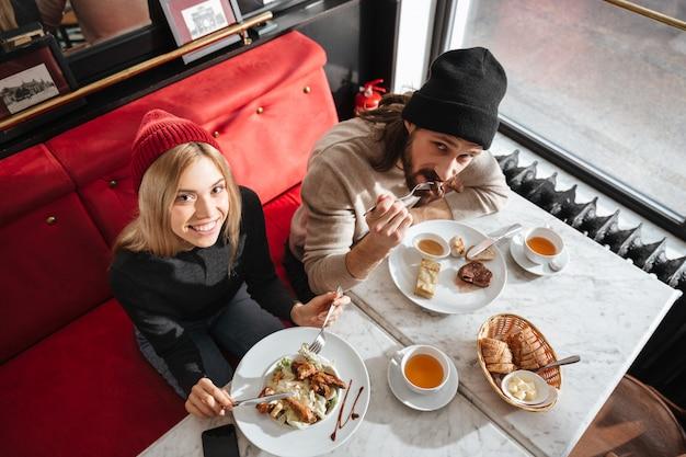 Vista superior de la pareja comiendo en la cafetería
