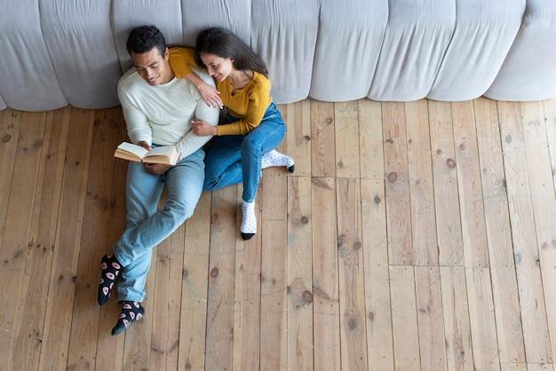 Vista superior de una pareja encantadora leyendo un libro