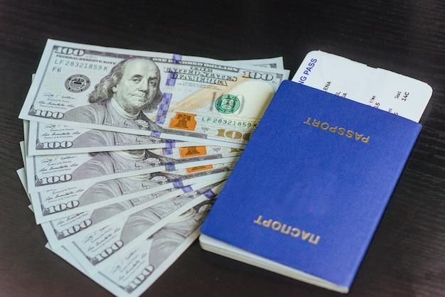 Vista superior del pasaporte con billetes de dólar en escritorio de madera.