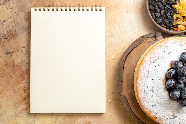 Vista superior de pasas tazón de pasas de pastel de pasas con uvas en el tablero blanco cuaderno
