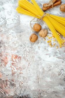Vista superior de pasta amarilla cruda con nueces en superficie clara