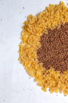 Vista superior de pasta cruda amarilla poco formada con trigo sarraceno en el escritorio blanco pasta comida italiana