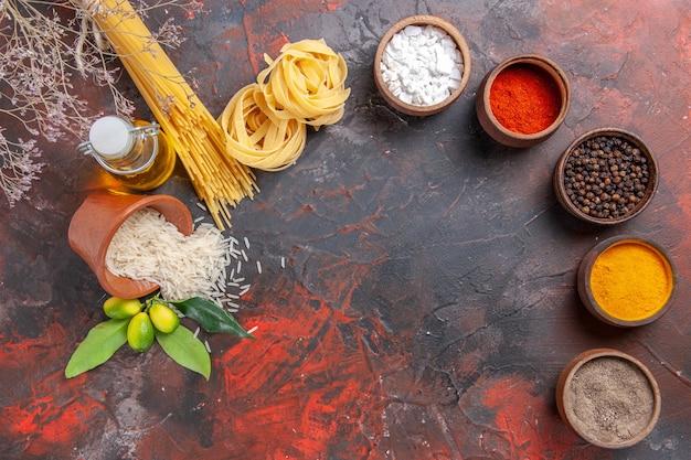 Vista superior de pasta cruda con condimentos de aceite y arroz sobre una pasta de masa cruda de superficie oscura