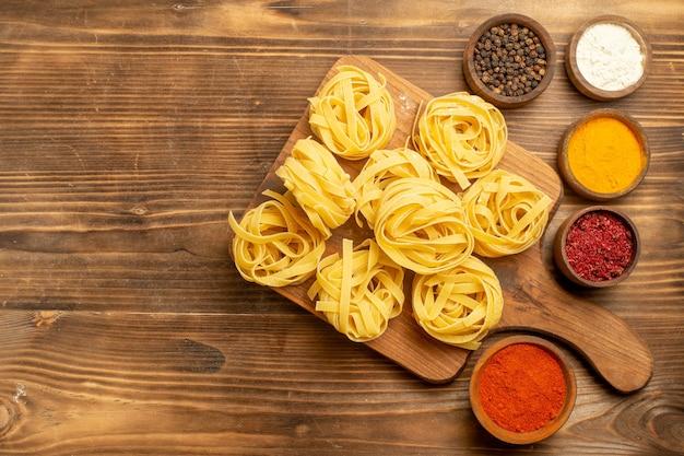 Vista superior pasta cruda diseñada pasta con condimentos en el fondo marrón pasta comida pasta