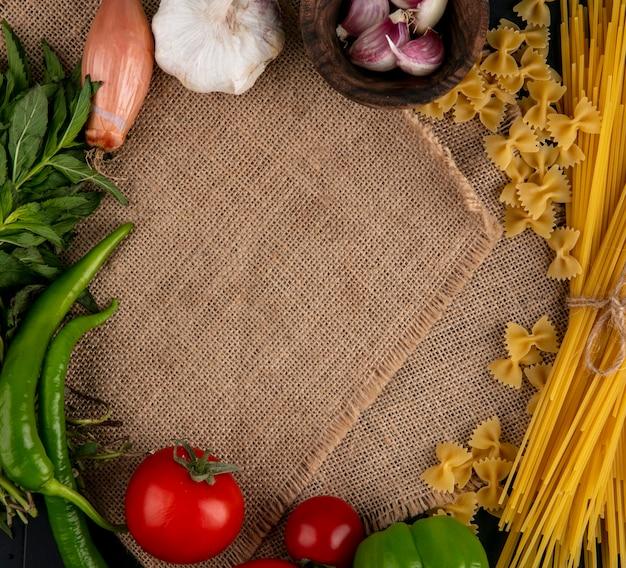 Vista superior de la pasta cruda con espaguetis crudos, tomates, cebollas y chiles en una servilleta beige
