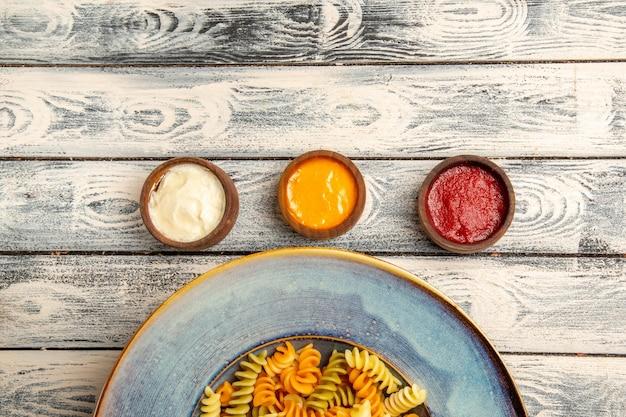 Vista superior de pasta espiral cocida con diferentes condimentos en el escritorio gris pasta color pimienta comida