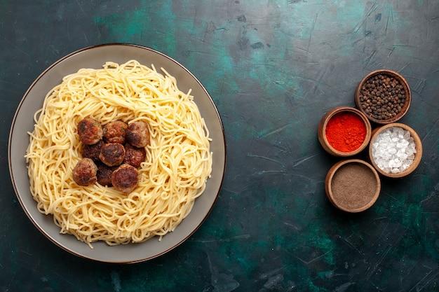 Vista superior de pasta italiana cocida con albóndigas y condimentos en la superficie azul oscuro