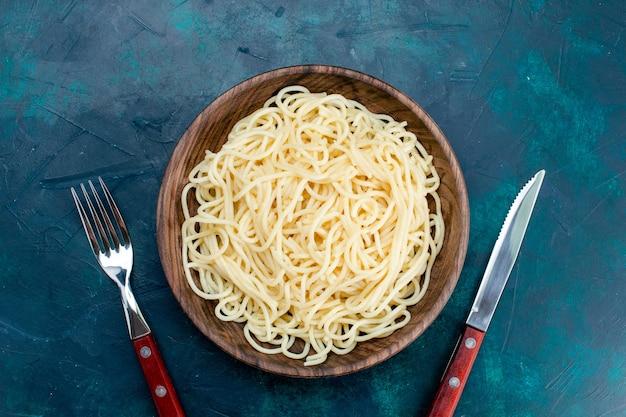 Vista superior de la pasta italiana cocida dentro de la placa de madera redonda sobre el fondo azul oscuro pasta italia comida cena masa carne