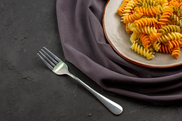 Vista superior de pasta italiana cocida pasta espiral inusual dentro de la placa en el escritorio oscuro comida de pasta cena comida plato de cocción