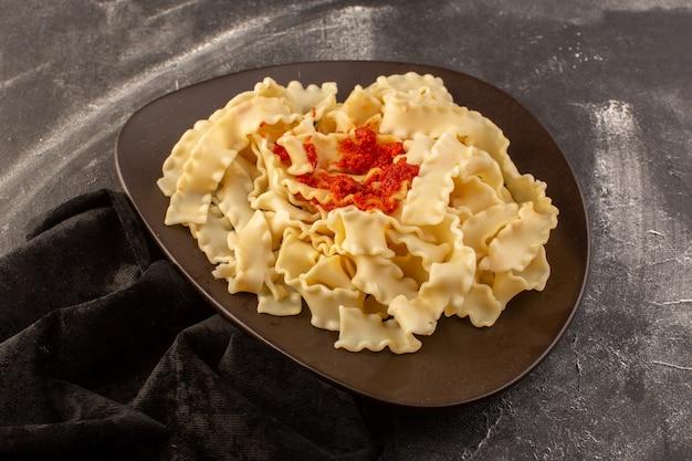 Una vista superior de pasta italiana cocida con salsa de tomate dentro de la placa oscura