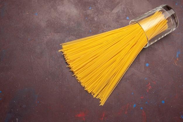 Vista superior de pasta italiana cruda formada largamente de color amarillo sobre el fondo oscuro pasta italia pasta comida color crudo