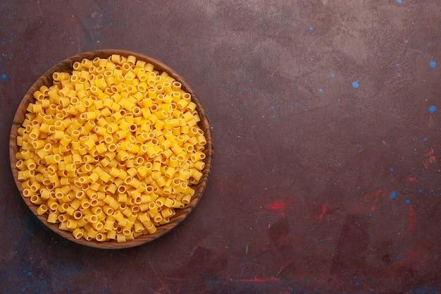 Vista superior de pasta italiana cruda poco formada dentro de la placa sobre fondo oscuro comida de pasta masa de alimentos muchos