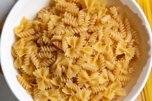 Una vista superior de pasta italiana cruda poco formada en el escritorio de madera pasta comida italiana