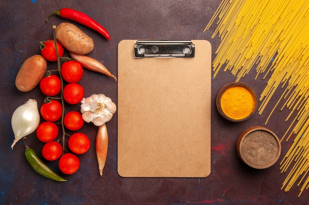 Vista superior de pasta italiana cruda con verduras frescas sobre fondo oscuro pasta de pasta italiana color de la comida