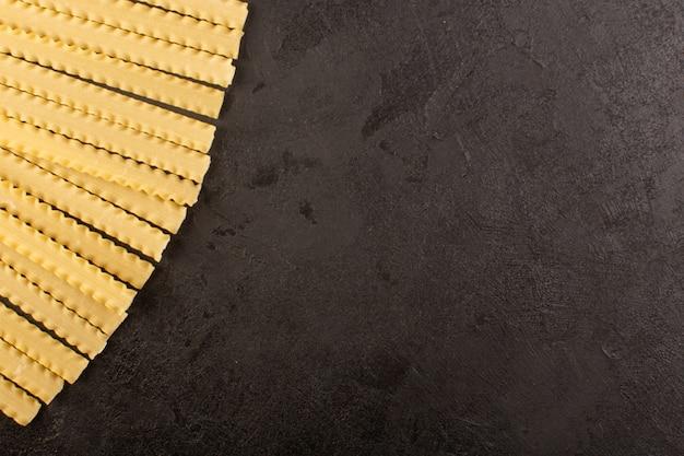 Una vista superior de pasta larga italiana cruda amarilla forrada en la oscuridad