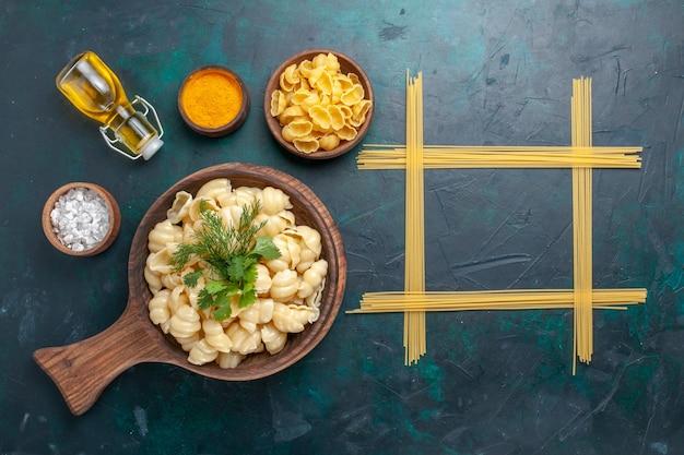 Vista superior de pasta de masa cocida con verduras y aceite de oliva sobre una superficie oscura