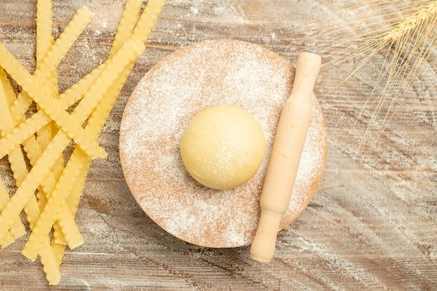 Vista superior de pasta de masa cruda con harina sobre fondo marrón de madera pasta de comida cruda de masa