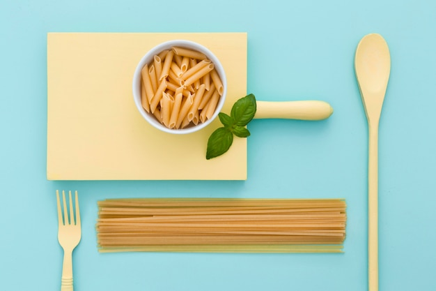 Vista superior de pasta orgánica con cubiertos en la mesa