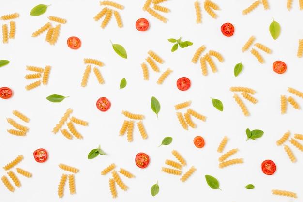 Vista superior pasta orgánica y tomates en la mesa