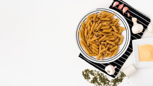 Vista superior de pasta penne cruda y sus ingredientes sobre fondo blanco