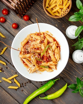 Vista superior de pasta penne con salsa de tomate y pimiento