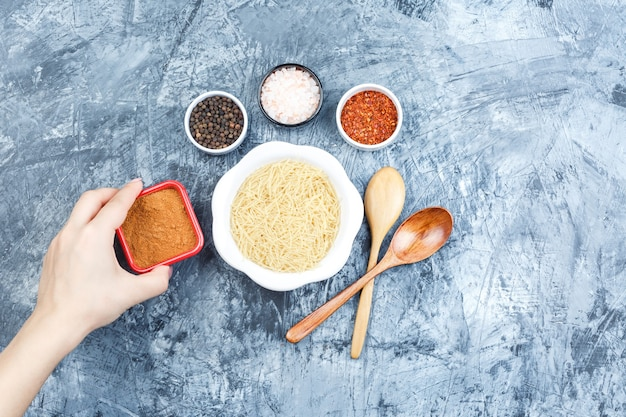 Vista superior de la pasta en un plato con especias y mano sujetando el cuenco de especias sobre fondo de yeso gris. horizontal