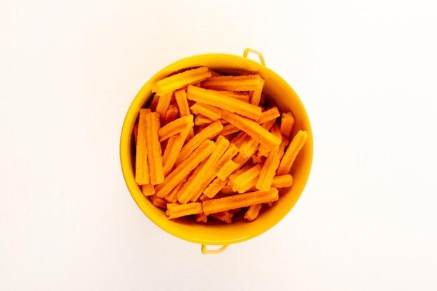 Una vista superior de pasta seca italiana raw orangepasta dentro del tazón en el blanco