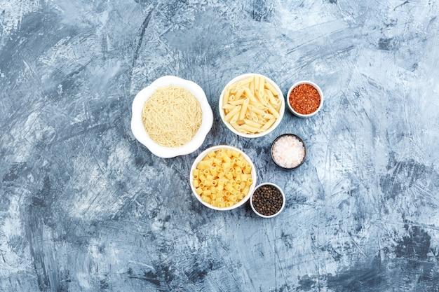 Vista superior de pasta surtida en tazones con especias sobre fondo de yeso gris. horizontal